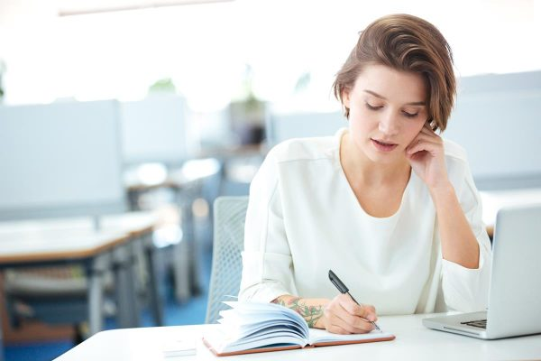 Businesswoman talking on the phone in office and writing notes